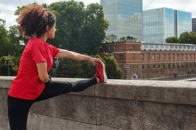 Side view of anonymous ethnic sportswoman in active wear with Afro hairstyle stretching leg on stone bridge during workout in front of buildings in town in daylight