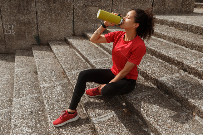 Side view of fit ethnic female athlete in sports clothes and smart watch drinking water from thermos while resting with closed eyes on staircase after training in sunlight