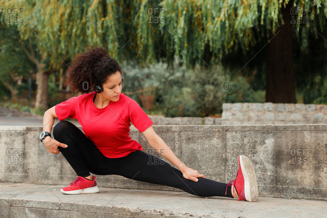 Pensive fit ethnic female athlete in active wear squatting while stretching leg and listening to music in wireless headset on embankment and looking away under cloudy sky