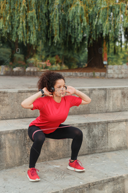 Side view of fit ethnic sportswoman in active wear and wearable bracelet doing squats using elastic tape while reaching arms on stairs under tree and listening to music from headphones