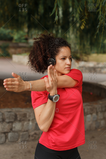 Young ethnic female athlete in red t shirt and smart watch stretching reached arm while training and listening to music in wireless headset near trees and looking away