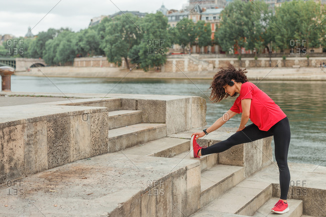 Concentrated ethnic female athlete in headphones and smart watch stretching leg during workout on embankment near river behind building in town under cloudy sky