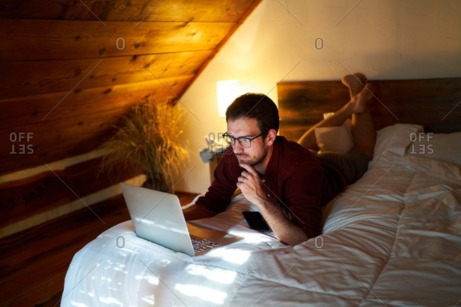 Thoughtful male entrepreneur in casual wear lying on bed and browsing netbook while working on remote project