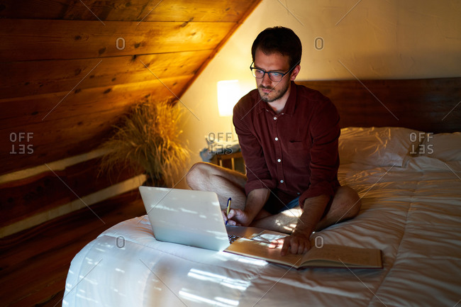 Busy male freelancer sitting on bed with laptop in cozy bedroom and writing in daily planner while working remotely at home