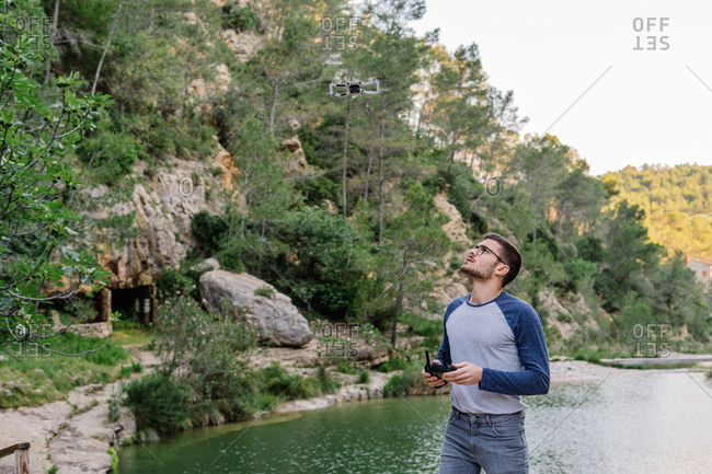 Concentrated male controlling modern drone flying on background of amazing mountainous landscape and lake