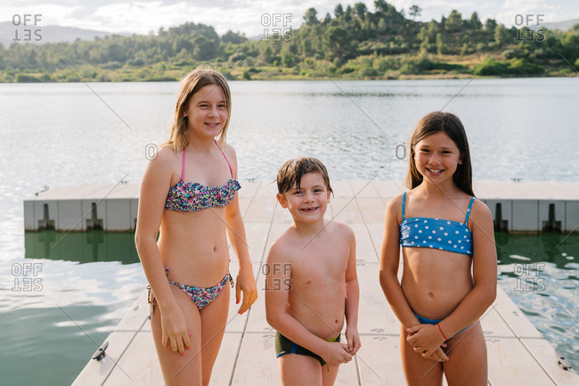 Smiling brother and sisters in swimwear standing on quay near lake and looking at camera while enjoying summer vacation