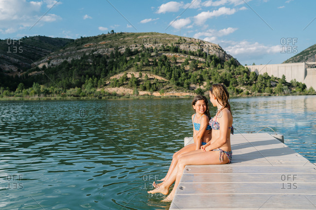 Side view of teen girls in swimwear sitting on wooden quay near lake and cheerfully looking at each other during vacation