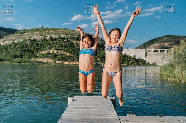 Children in swimwear jumping on wooden quay near pond during weekend in summer