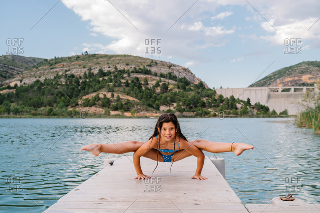 Smiling child in bikini doing yoga in Tittibhasana on quay near lake and looking at camera