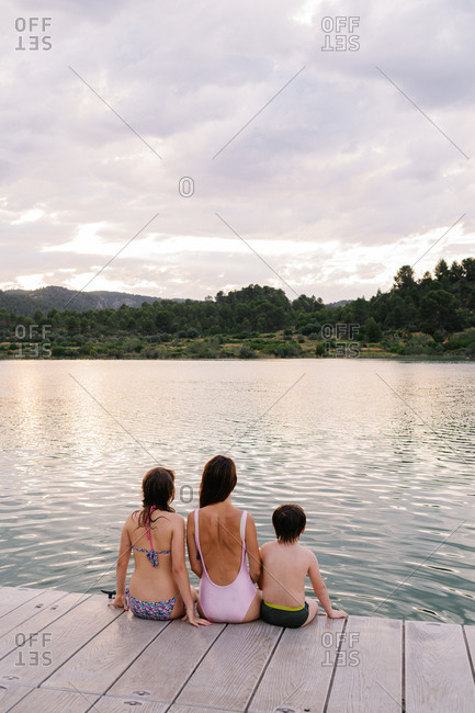 Back view of carefree siblings in swimwear sitting on pier and admiring majestic scenery of pond while enjoying summer vacation