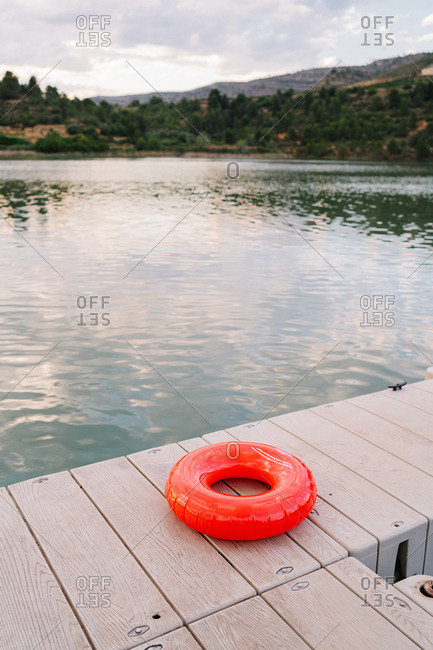 Inflatable ring placed on wooden quay near pond on background of majestic sunset sky
