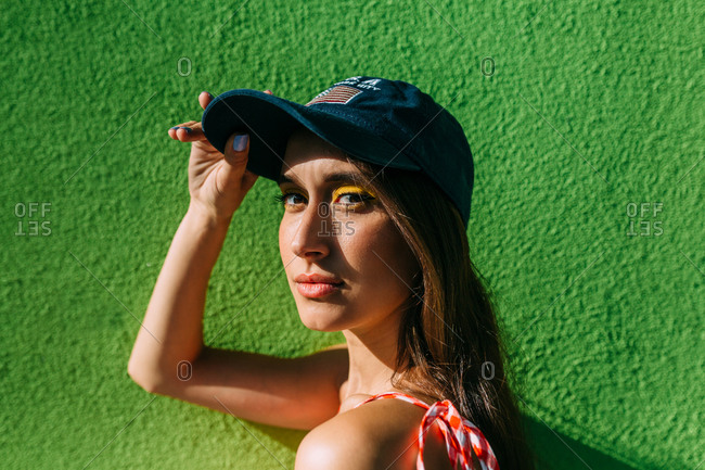 Portrait of brunette girl with long hair and cap looking at camera in front of green background