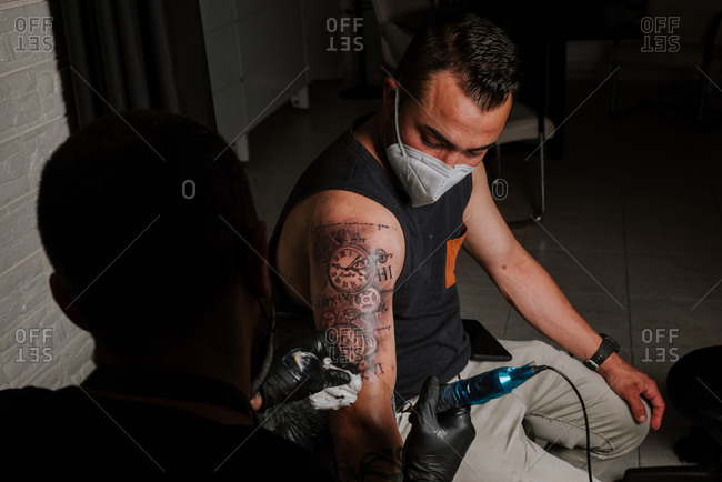Back view of male with face mask master tattooing client lying in chair near floor lamp in tattoo parlor while using tattoo machine