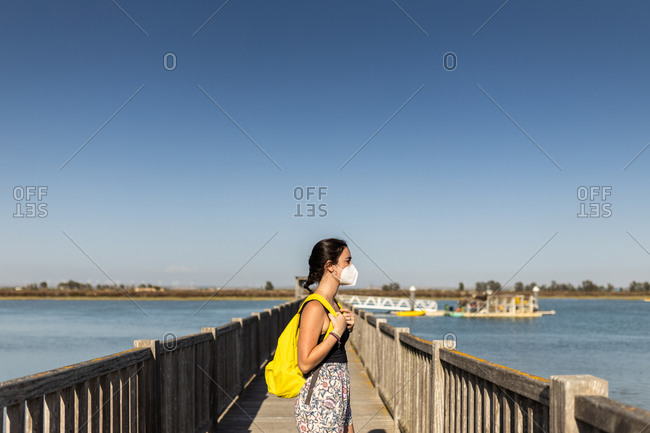 Young woman with yellow backpack and face mask on a pier on her way to her next trip, looking to the right