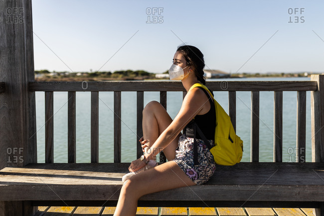 Young woman with yellow backpack and face mask sit down on a pier on her way to her next trip, looking to the left