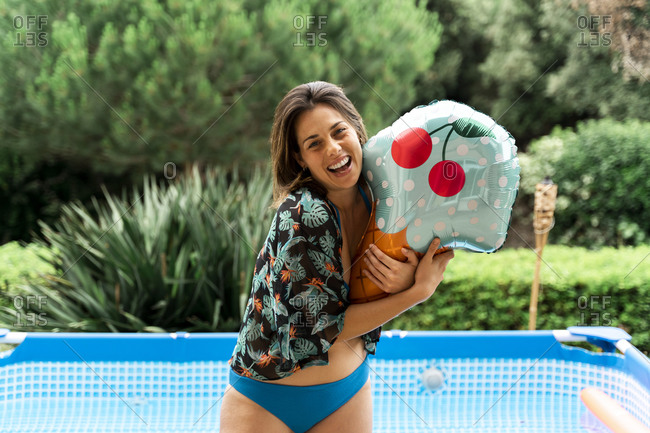 Cheerful young woman holding ice cream toy with inflatable swimming in background