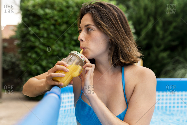 Beautiful woman drinking orange juice in inflatable swimming pool at yard