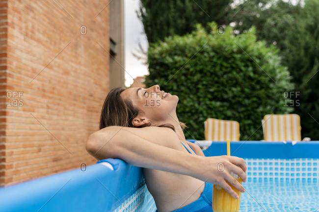 Relaxed woman holding orange juice in inflatable swimming pool at yard