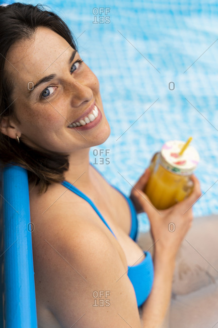 Happy woman holding orange juice in inflatable swimming pool at yard