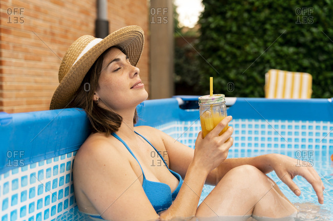 Woman holding orange juice while relaxing in inflatable swimming pool at yard