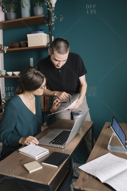 Young man and woman discussing paper in home office