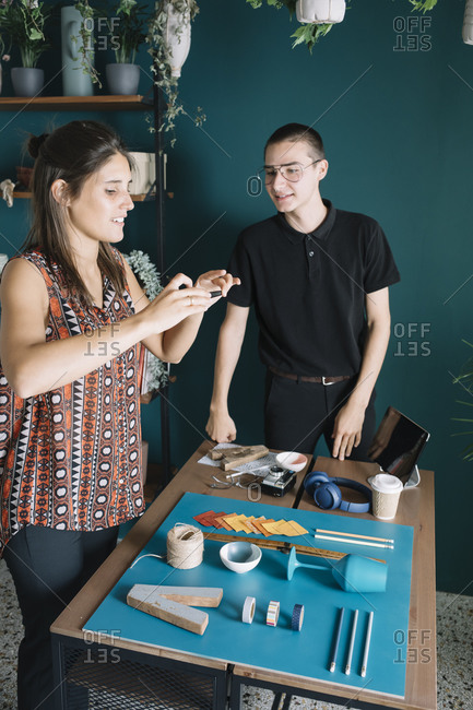 Young creative couple taking smartphone picture of decoration on table