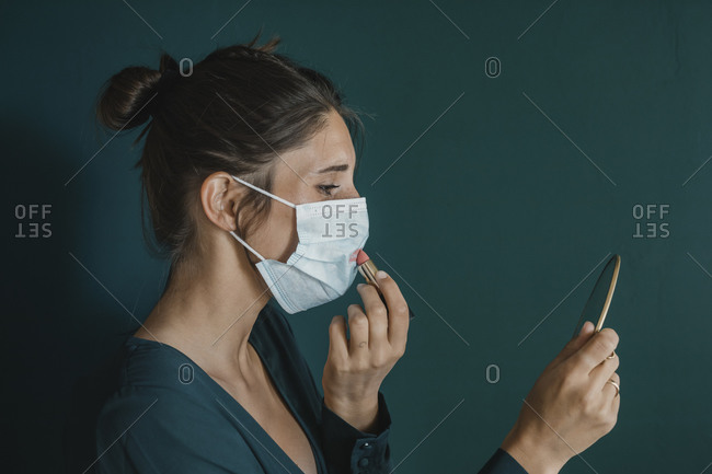 Young Woman Putting Makeup On Protective Mask