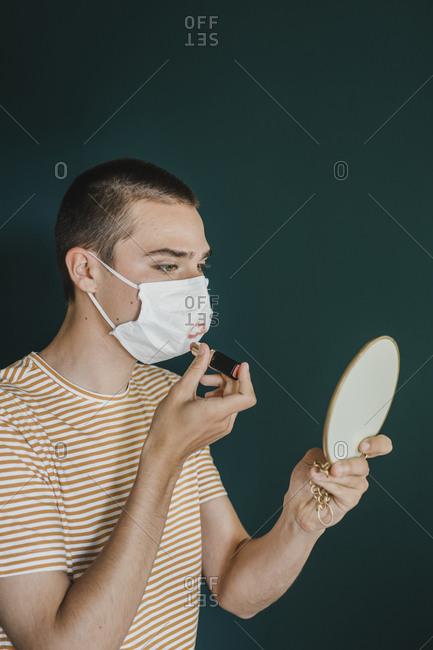 Young Man Putting Makeup On Protective Mask