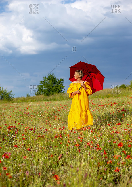 Mature woman with red umbrella standing amidst poppies against sky