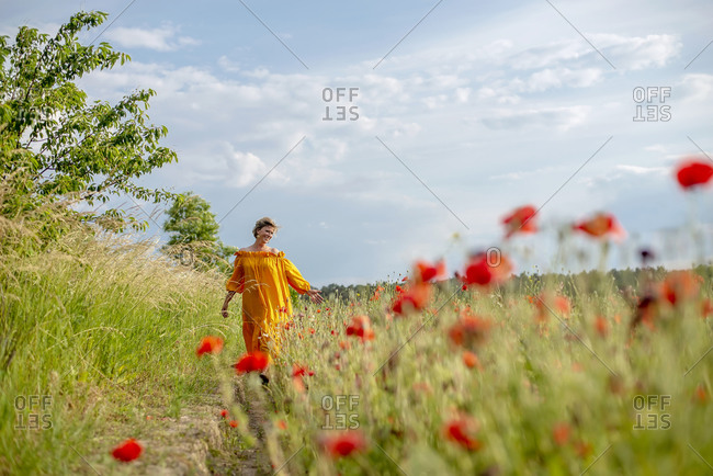 Happy mature woman walking amidst poppy field against sky