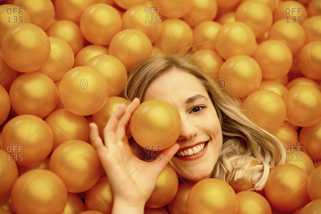 Close-up of smiling beautiful woman lying in orange ball pit