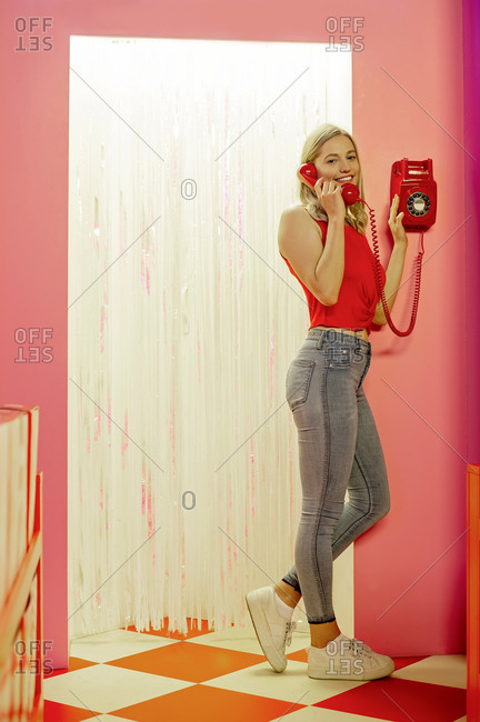 Smiling young woman talking over telephone while standing indoors