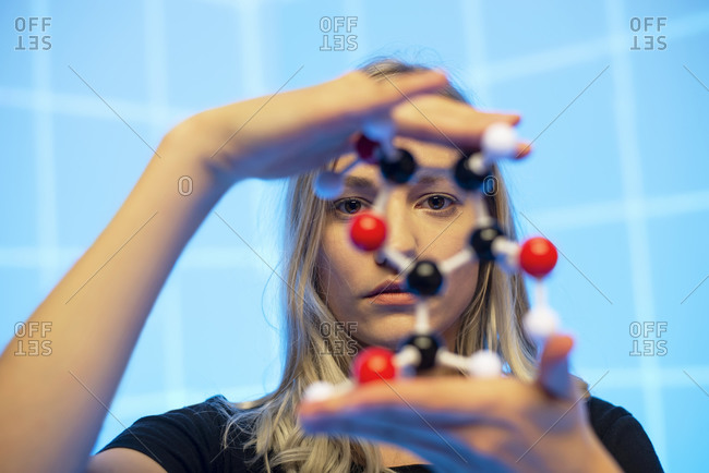 Close-up of young female scientist holding molecule model against blue grid pattern