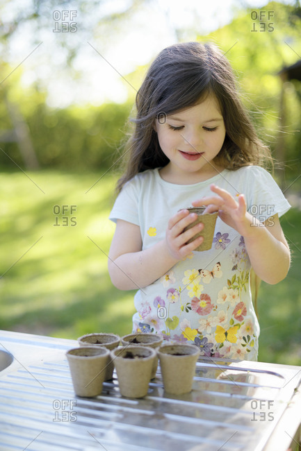Cute girl planting seeds in small pots on table at garden