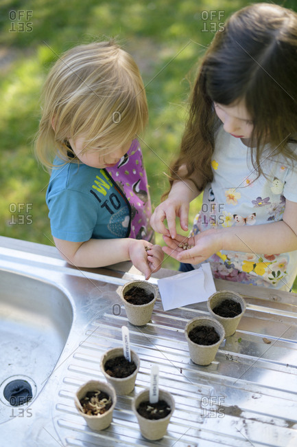 Girls planting seeds in small pots on table at garden