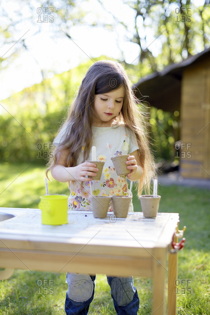 Cute girl planting seeds in small pots while standing at table in yard