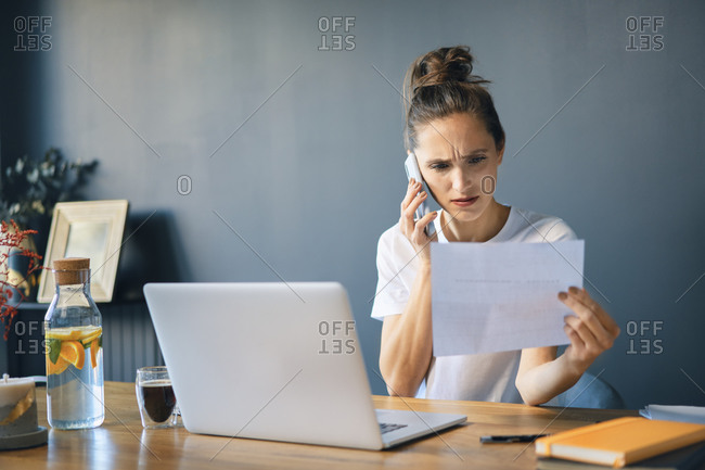 Businesswoman holding document talking over smart phone while sitting at desk in home office