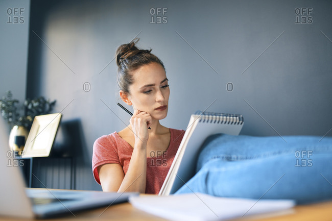 Businesswoman with note pad and pencil relaxing at desk in home office