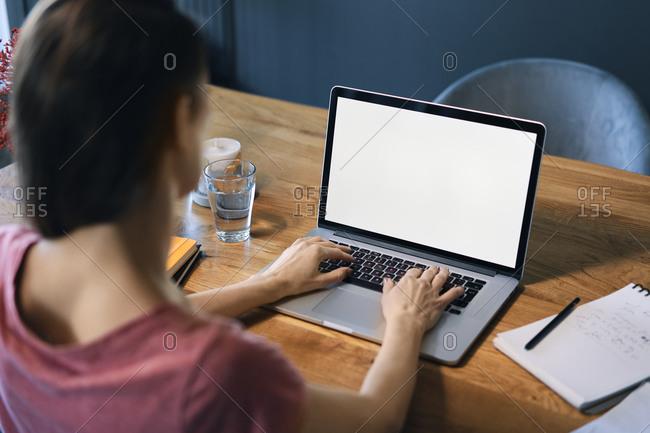 Female freelancer using laptop on desk in home office
