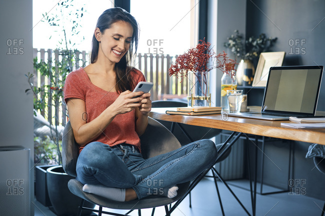 Female entrepreneur using smart phone while sitting on chair by desk in home office