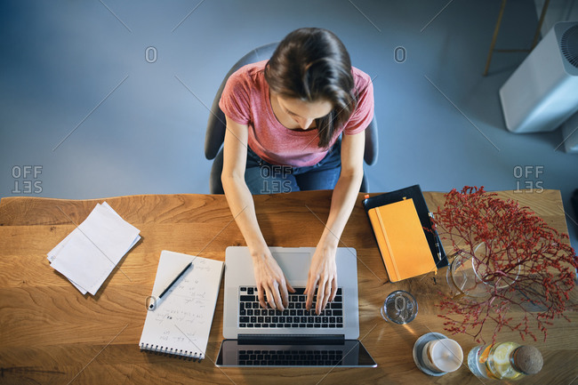 Female freelancer working over laptop on desk while sitting in home office