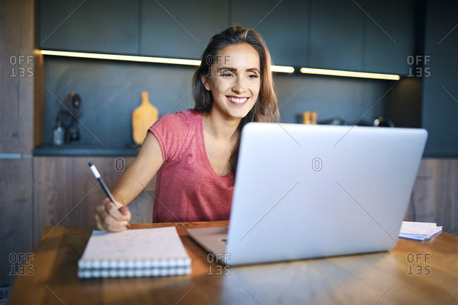 Smiling female entrepreneur looking at laptop while writing in note pad on desk