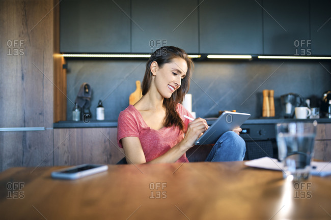 Smiling female entrepreneur using digital tablet while sitting at desk in home office