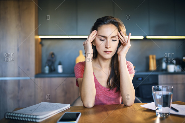 Female entrepreneur with head in hands sitting at desk