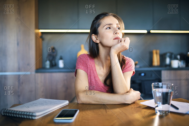 Thoughtful female entrepreneur looking away while sitting at desk in home office