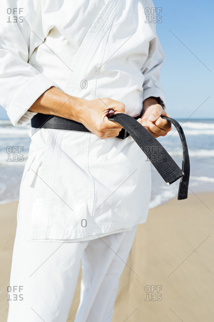 Close-up of mature man tying black belt while standing at beach