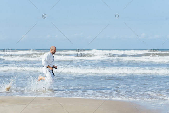 Mature man wearing karate gi running at beach against sky during sunny day