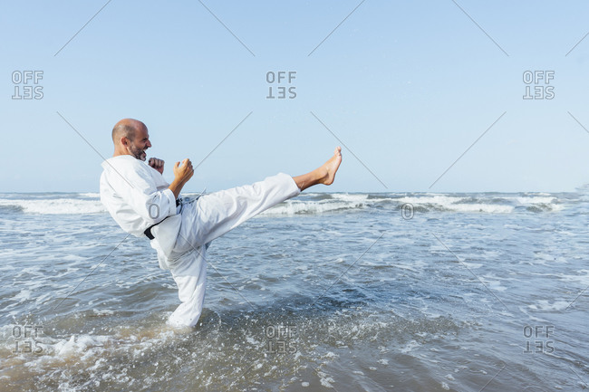 Mature man kicking while practicing karate in sea against clear sky