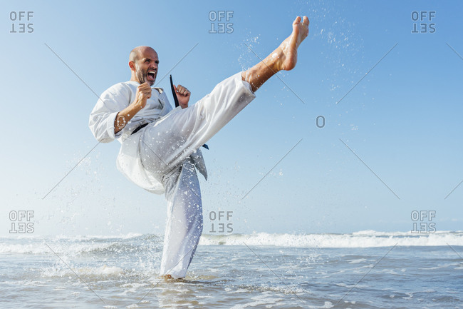 Mature man screaming while practicing karate in sea against clear sky