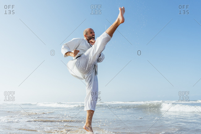 Man screaming while practicing karate in sea against clear sky
